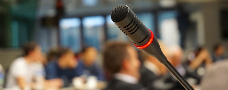 Microfoon in conferentieruimte met deelnemers vaag op de achtergrond
