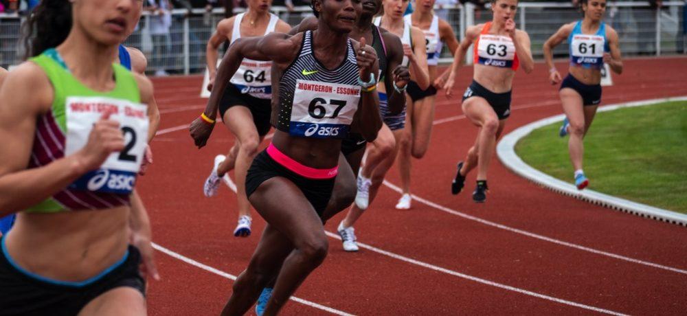 Rennende dames in de bocht op de atletiekbaan